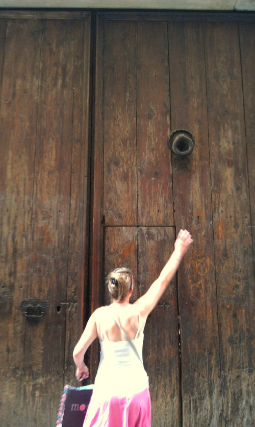 Were the ancient Catalonians really tall? Are doors the windows to a house's soul? This visitor reaches for the knob to no avail. Senorita, there's a small door right in front of you.    Photo by Heather Granahan